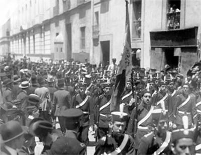 Estudiantes militarizados de la Escuela Nacional Preparatoria desfilan por una calle de la Cd. de México