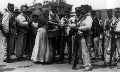 Mujer reparte pan a unos soldados en la estación de Buenavista
