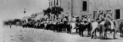Revolucionarios a caballo en una calle