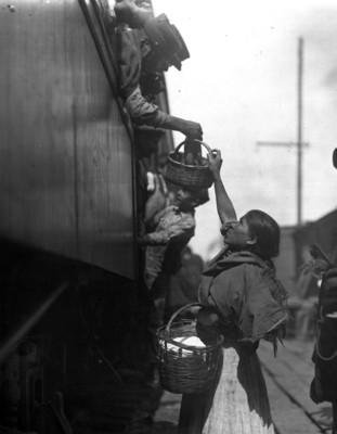 Mujer entrega comida a un soldado a través de la ventanilla de un vagón