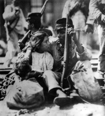 Soldadera sentada en el suelo con su esposo e hijo