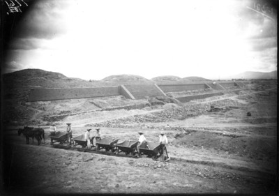 Hombres sobre vagonetas durante los trabajos de exploración en la Ciudadela, Teotihuacán, reprografía