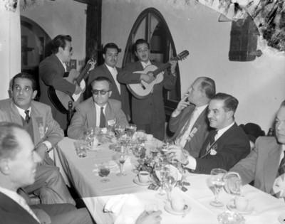 Trio canta ante hombres durante banquete