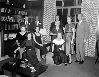 Hombres y mujeres durante reunión social en la sala de una casa, retrato de grupo