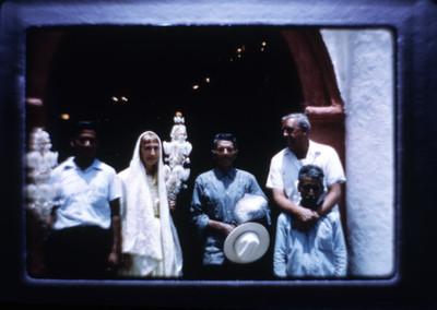 Hombres y mujer de pie afuera de iglesia, retrato de grupo