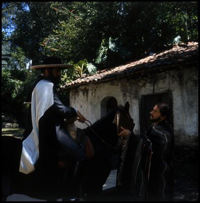 Farnesio de Bernal entrega carpeta con documentos a otro actor, escena de la película El Señor de Osanto