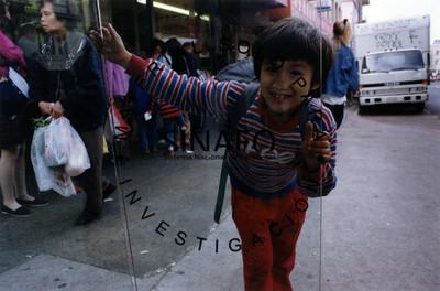 Niño se recarga sobre puerta de vidrio