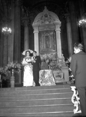 Novios junto al altar principal de una iglesia