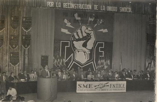 Rafael Galván, Agustín Sánchez Delint, Rodolfo Calderón y otros personajes presiden una asamblea de la Federación Nacional de Trabajadores de la Industria y Comunicaciones Eléctricas
