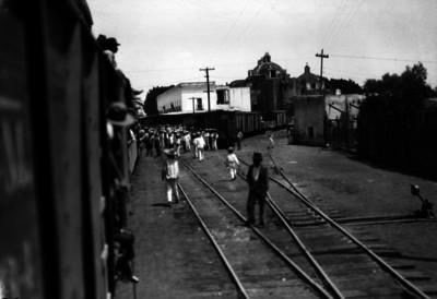 Gente en una estación de ferrocarril en un poblado
