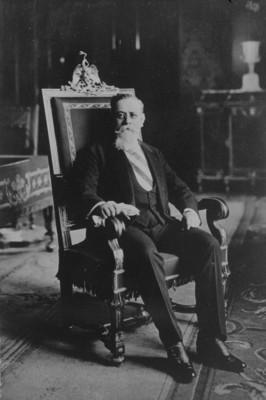 Venustiano Carranza sentado en la silla presidencial, retrato
