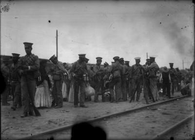 Soldados en descanso comen junto a vías de tren