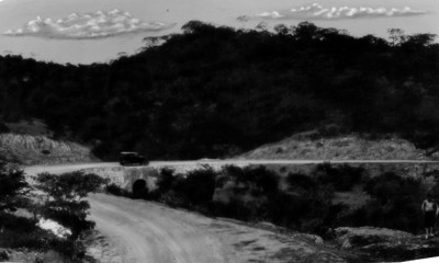 Hombre a pie y vehículo, circulan por carretera en un paraje