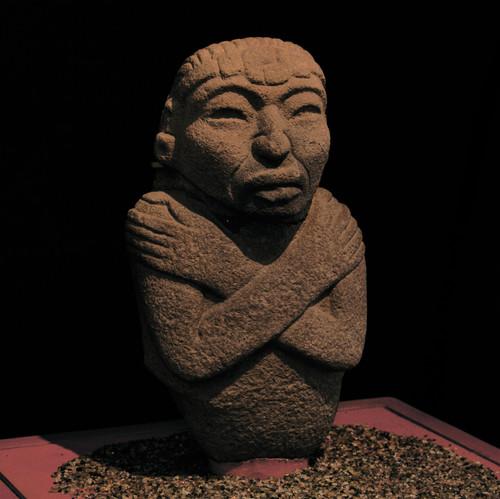 Escultura antropomorfa con brazos cruzados