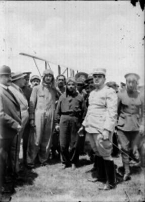 Pilotos con militares y otras personas en un campo aéreo