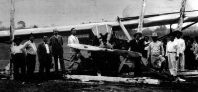 Hombres junto a los restos un avión accidentado, retrato de grupo