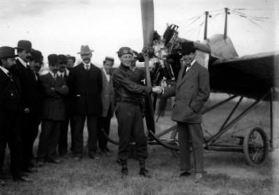 Rodolfo Gaona y George Dyot saludándose junto a un Deperdussin