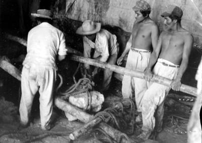 Trabajadores trasladan una piedra en el interior del Templo de las Inscripciones