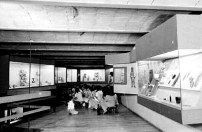 Estudiantes sentadas, algunas al piso, observan exposición de la planta alta de sala de Oaxaca