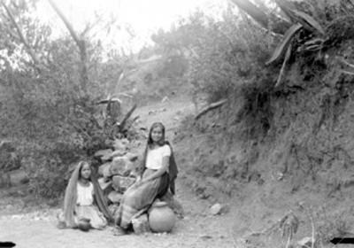 Mujeres con ollas de agua en un camino