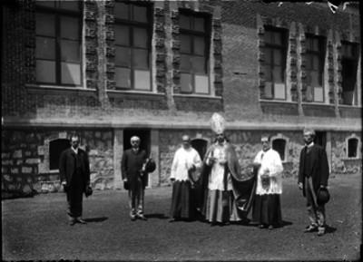 Ernesto Pugibet acompañando a un arzobispo en los patios de la fábrica El Buen Tono, durante su bendición, retrato de grupo